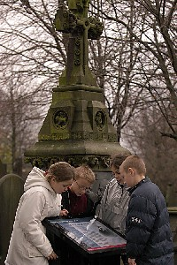 Children from Godfrey Ermen C of E primary school studying a heritage trail display board at Weaste Cemetery