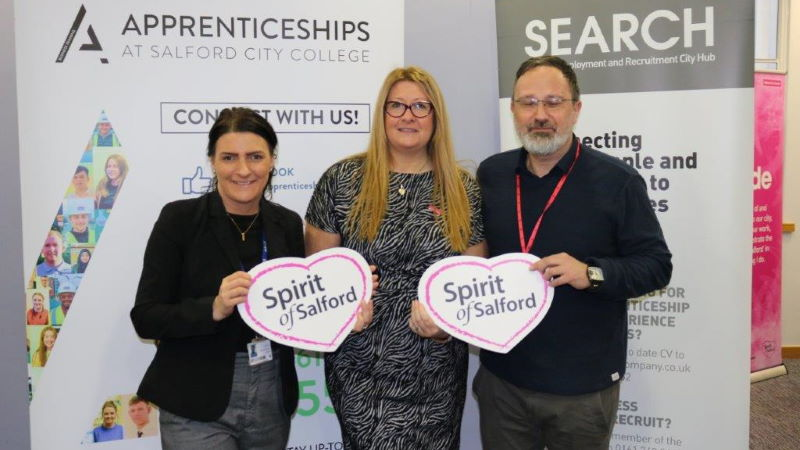 Three people holding Spirit of Salford cards
